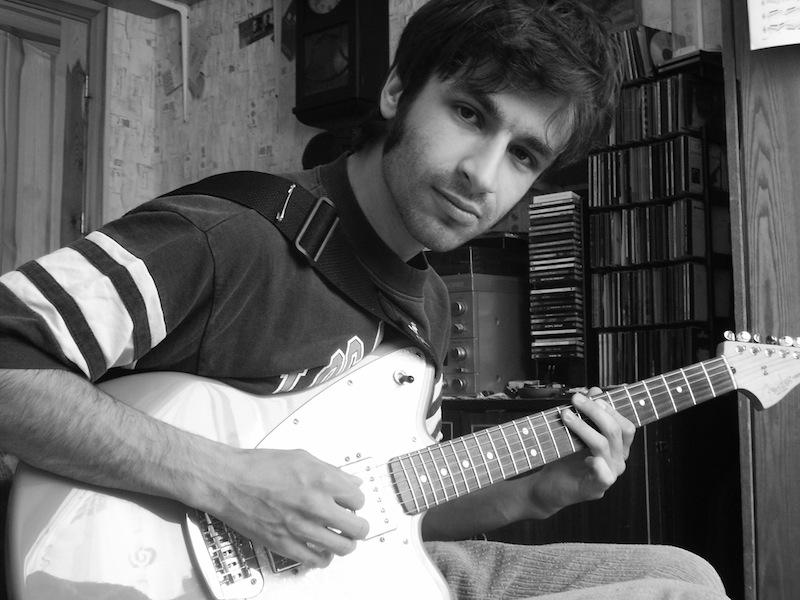 Oskras Herliņš spēlē ģitāru